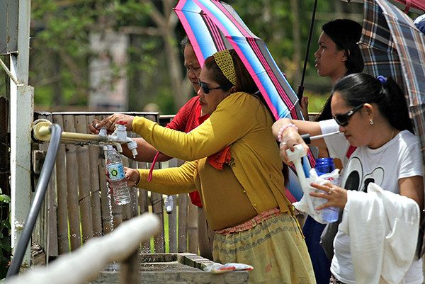 Pilgrims fill container with holy water